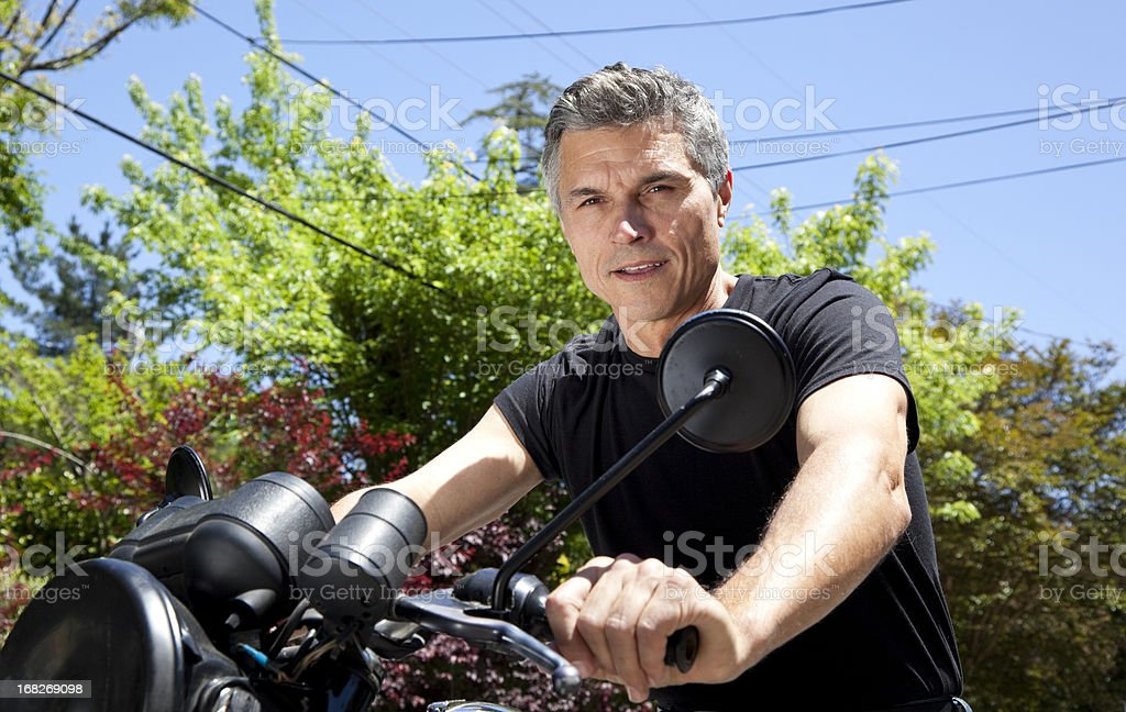 mature man on motorcycle stock photo