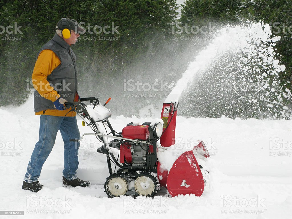 Mature man operating a snow blower. stock photo