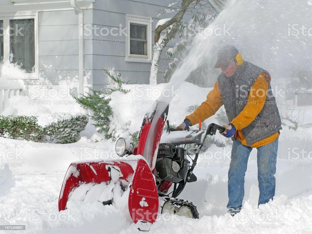 Mature man operating a snow blower. stock photo