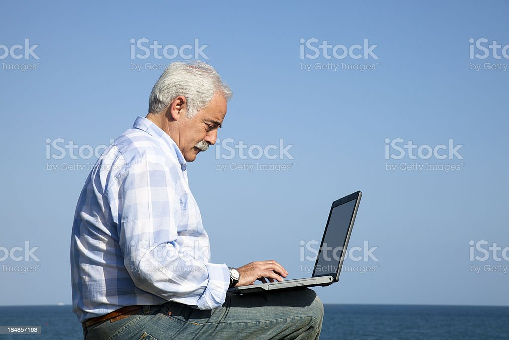 Mature man outdoors with laptop royalty-free stock photo