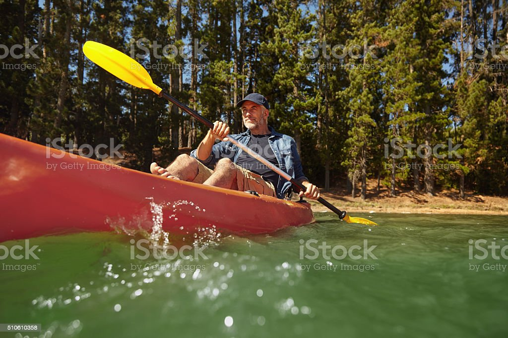 Mature man paddling a kayak in a lake stock photo