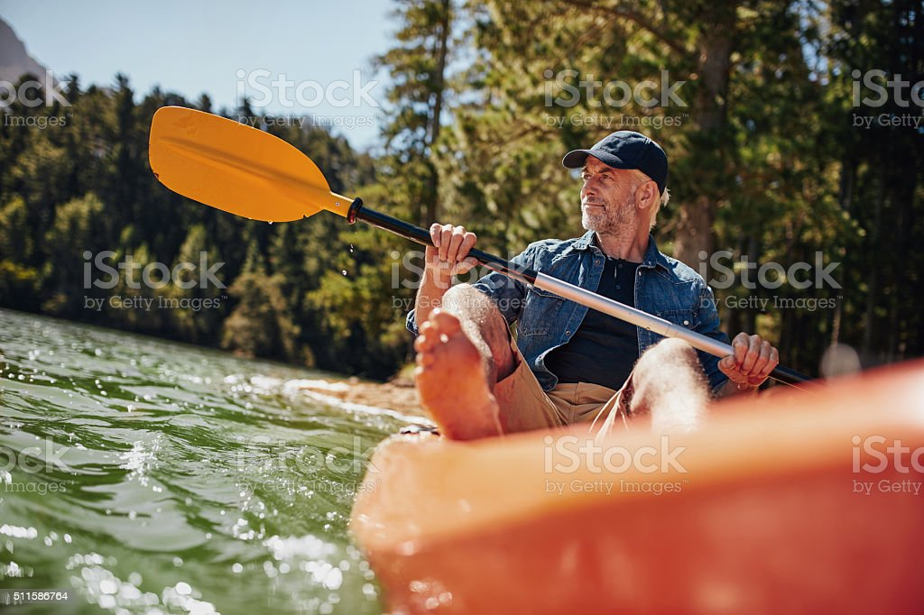 Mature man paddling a kayak stock photo