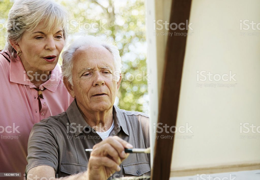 Mature man painting on canvas with his wife royalty-free stock photo