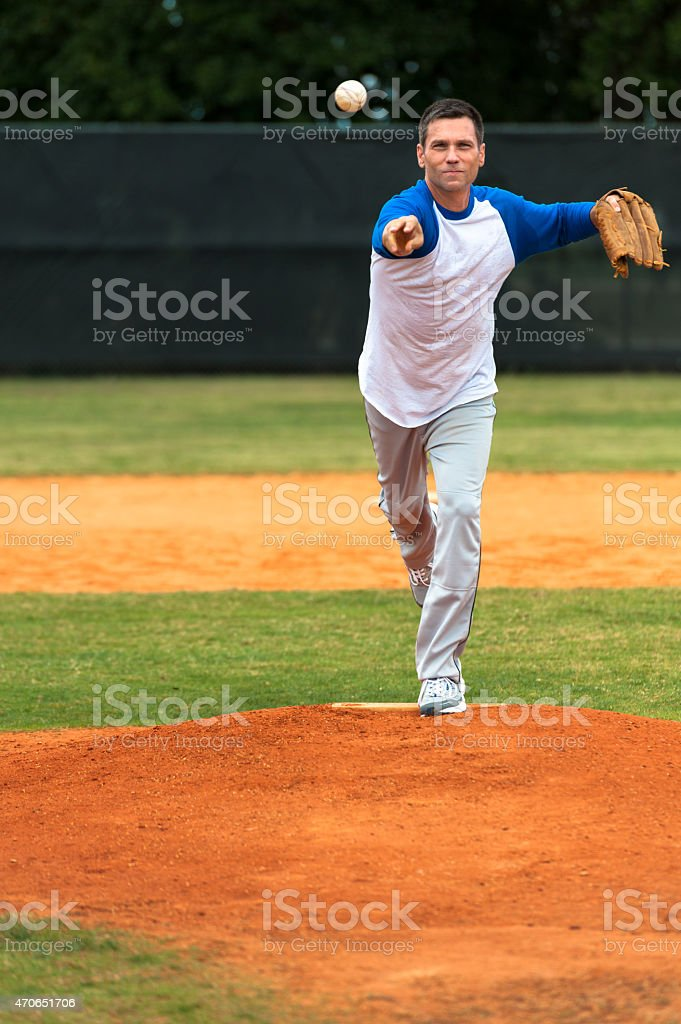 Mature man pitching baseball stock photo