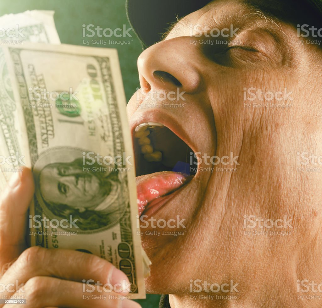 Mature man playfully licking bundle of $100 banknotes stock photo