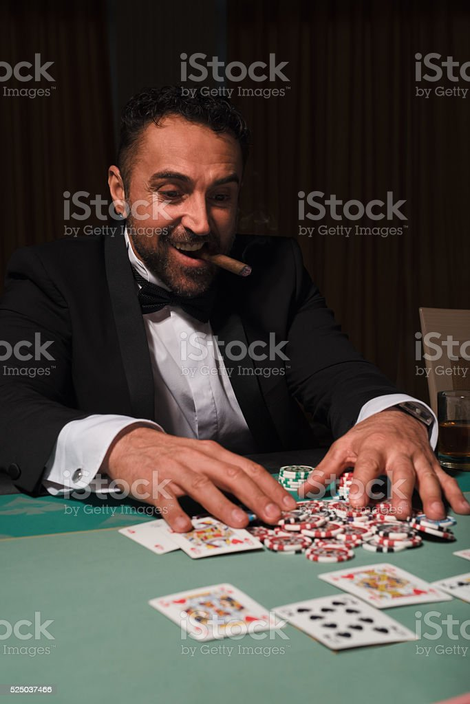 Mature man playing cards at the casino stock photo