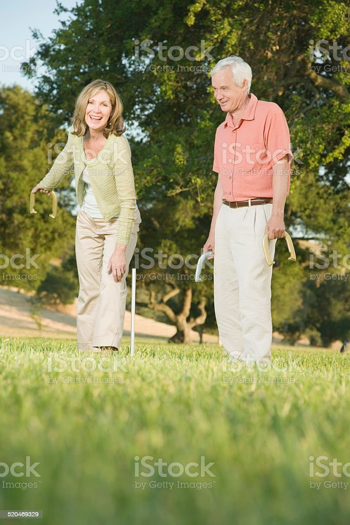 Mature man playing game of horseshoes stock photo