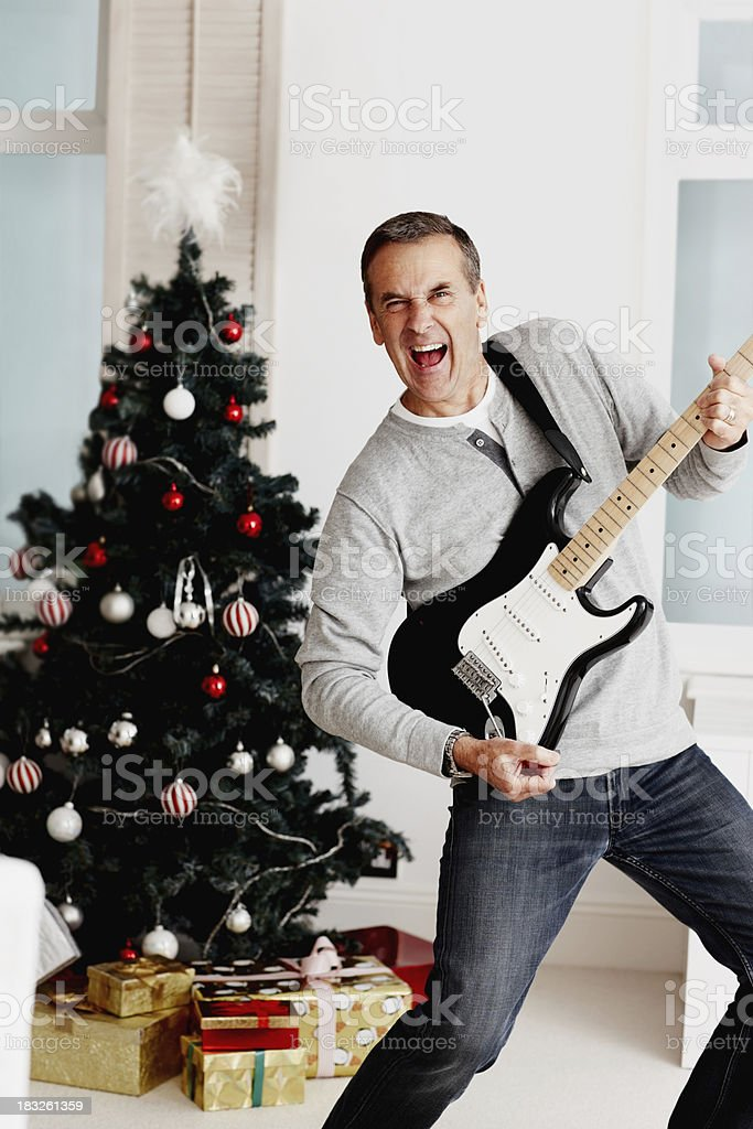 Mature man playing guitar with Christmas tree in background royalty-free stock photo