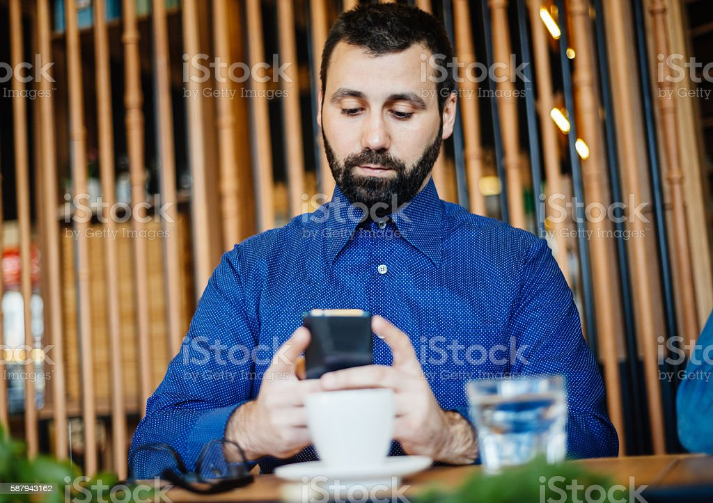 Mature man playing mobile gaming app during coffee break stock photo