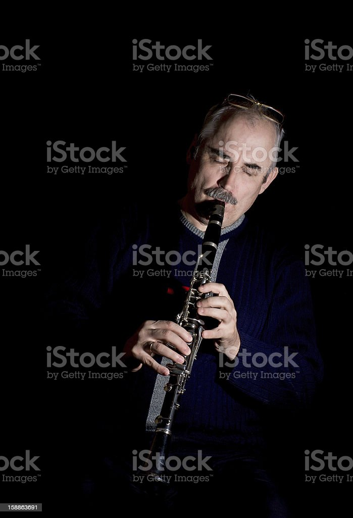 Mature man playing the clarinet jazz stock photo