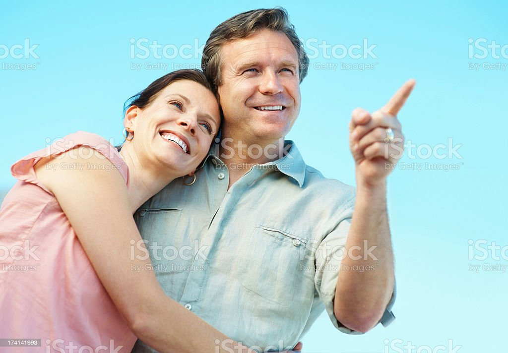 Mature man pointing something out to a cute woman stock photo