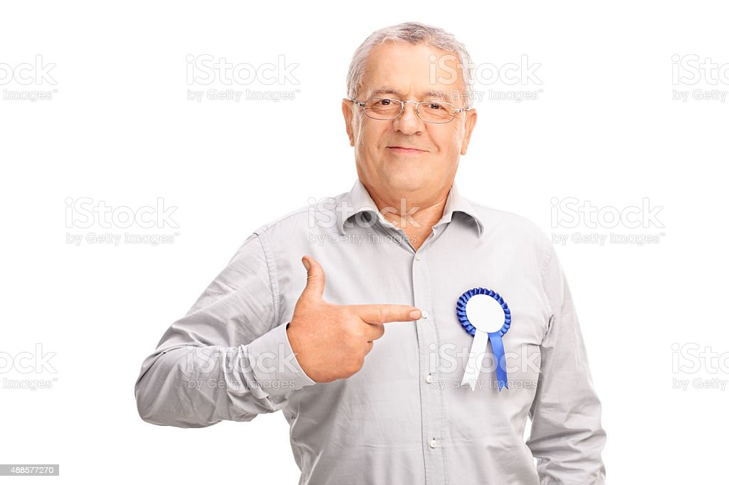 Mature man pointing to a badge on his shirt stock photo