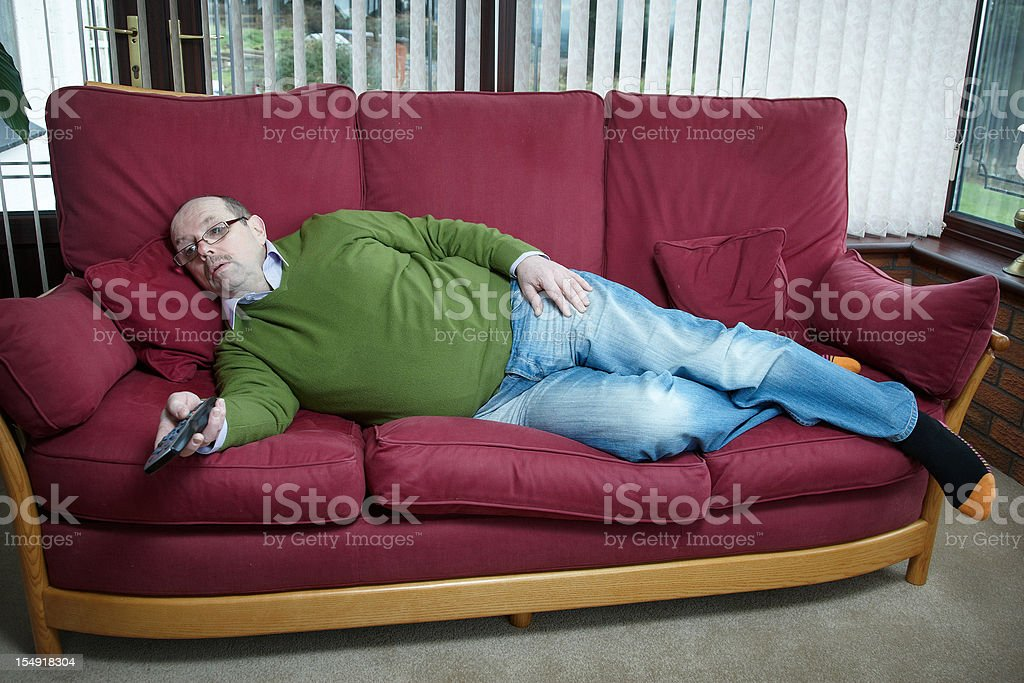Mature man portrait lying on sofa with TV remote stock photo