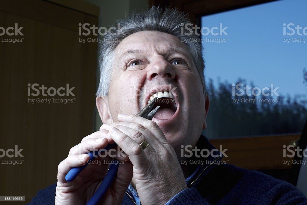 Mature man pulling out own teeth with pliers stock photo