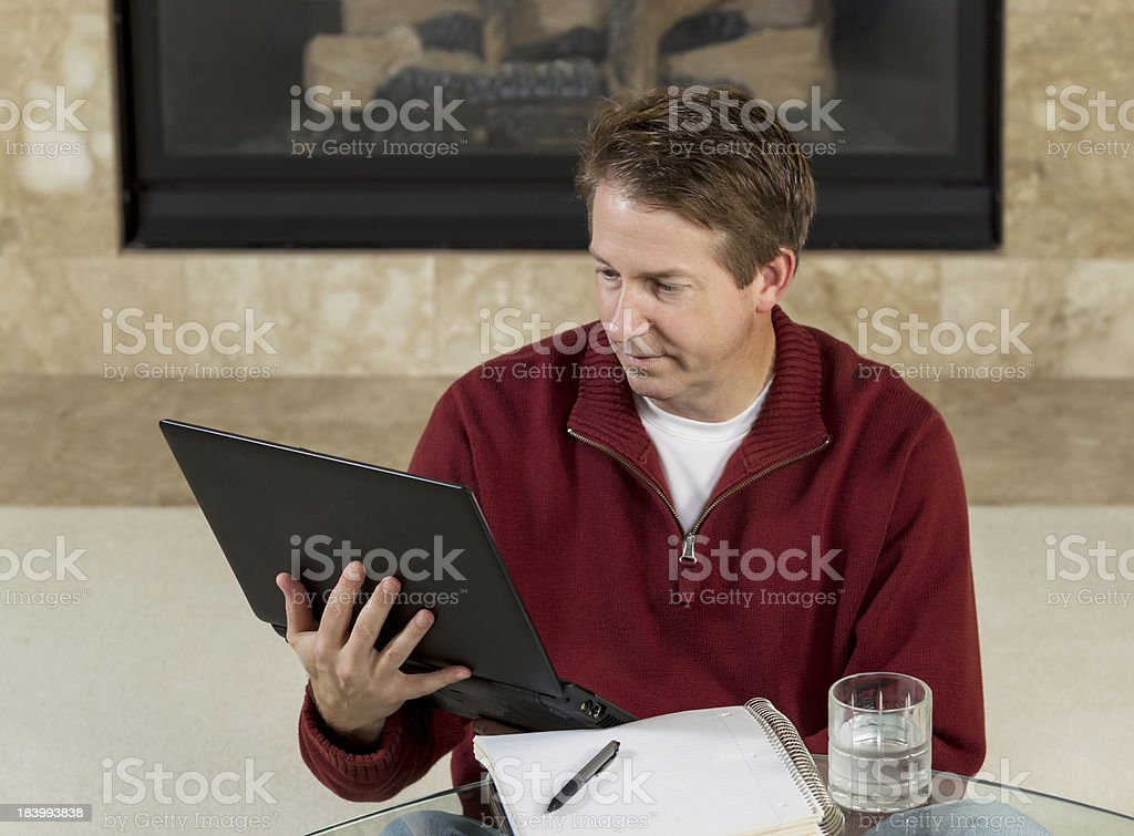 Mature man reading information from his computer while at home royalty-free stock photo
