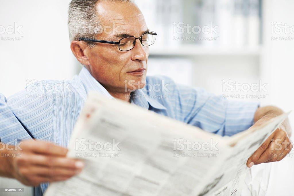 Mature man reading newspaper. royalty-free stock photo