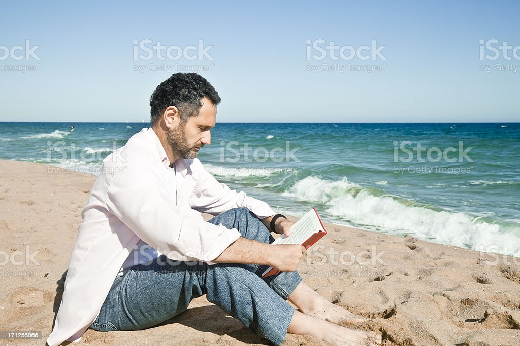 Mature man reading on a beach royalty-free stock photo