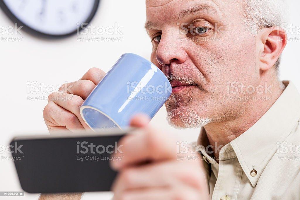 mature man reading on his smartphone screen stock photo
