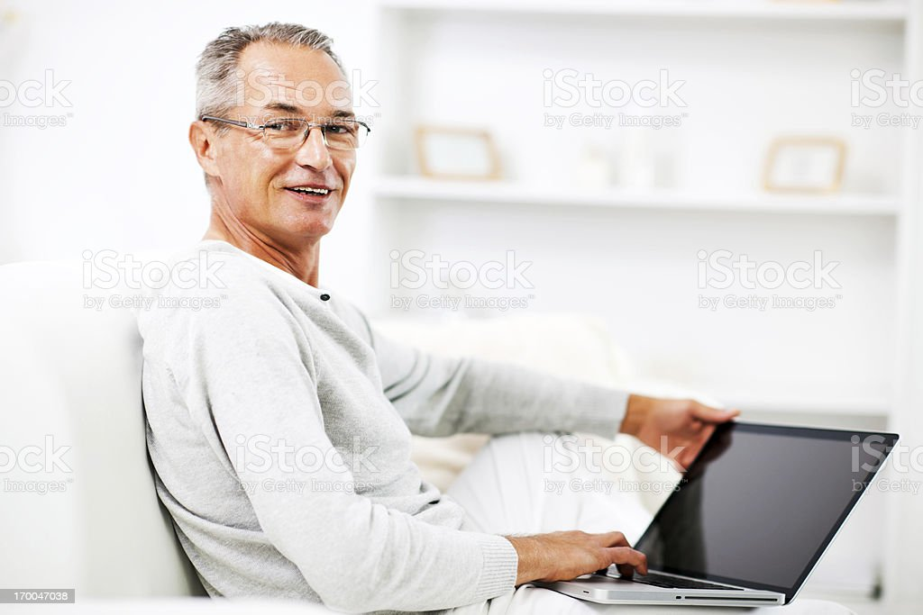 Mature man relaxing at home with his laptop royalty-free stock photo