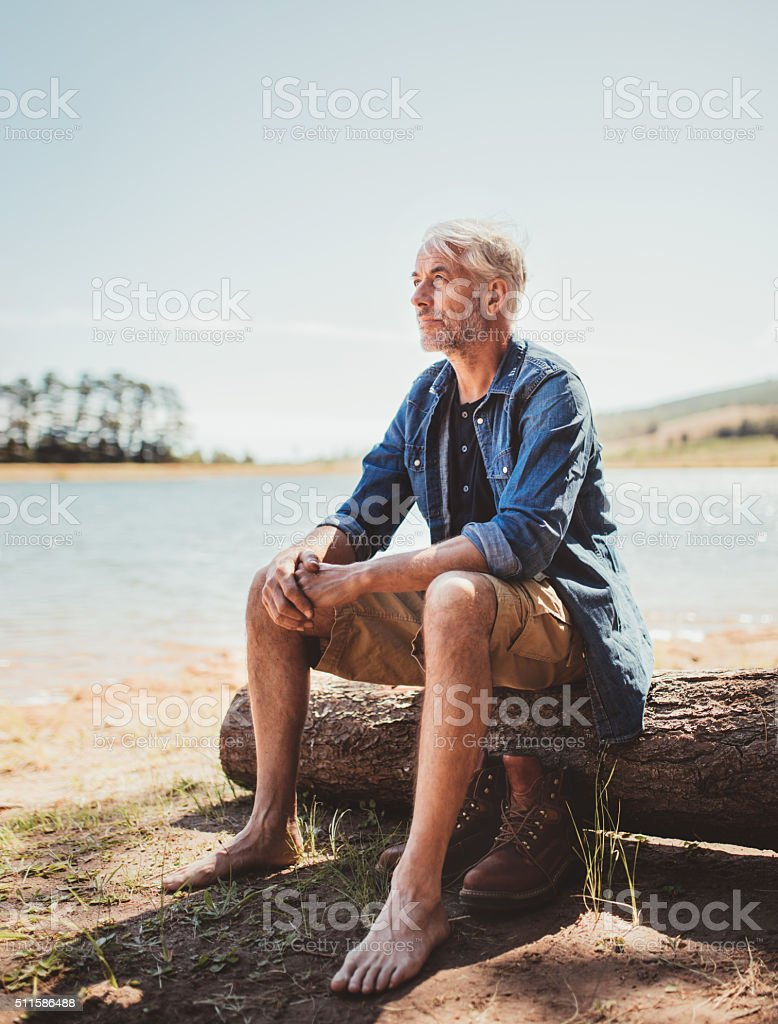 Mature man relaxing by a lake stock photo