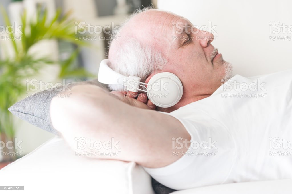 mature man relaxing with music on the sofa stock photo