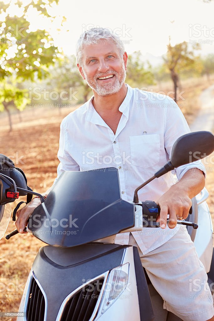 Mature Man Riding Motor Scooter Along Country Road stock photo