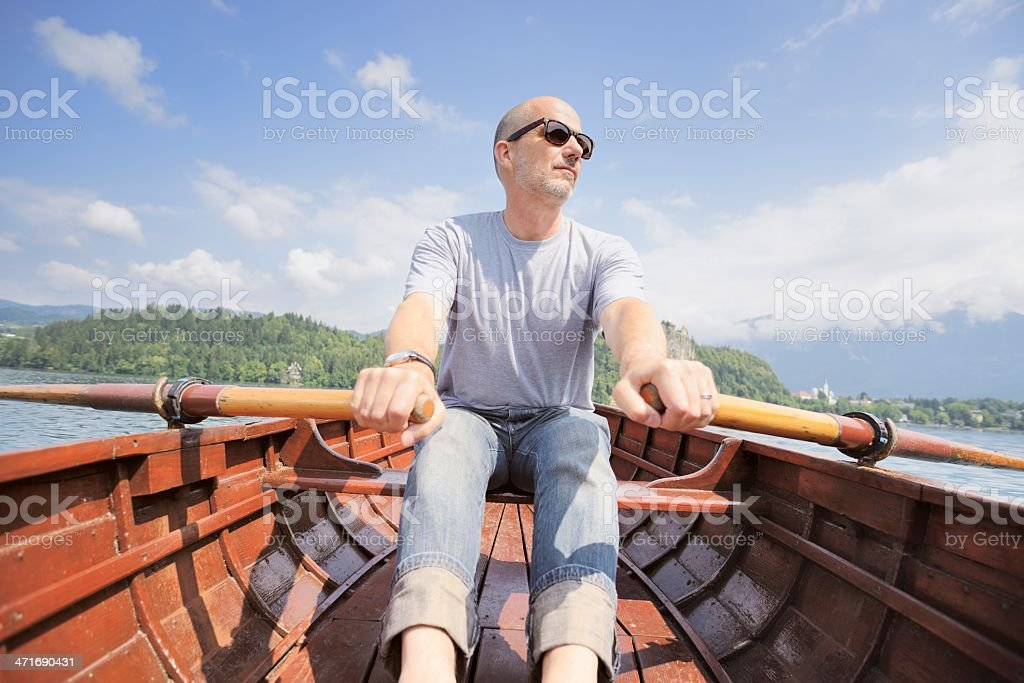 Mature Man Rowing Wooden Boat on Lake royalty-free stock photo