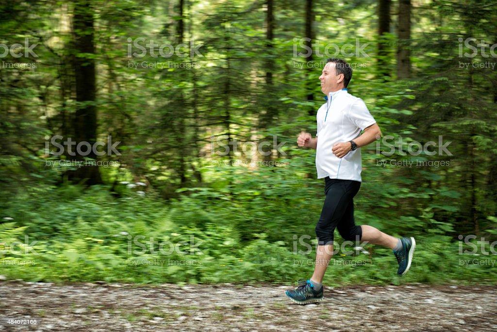 mature man running in nature stock photo