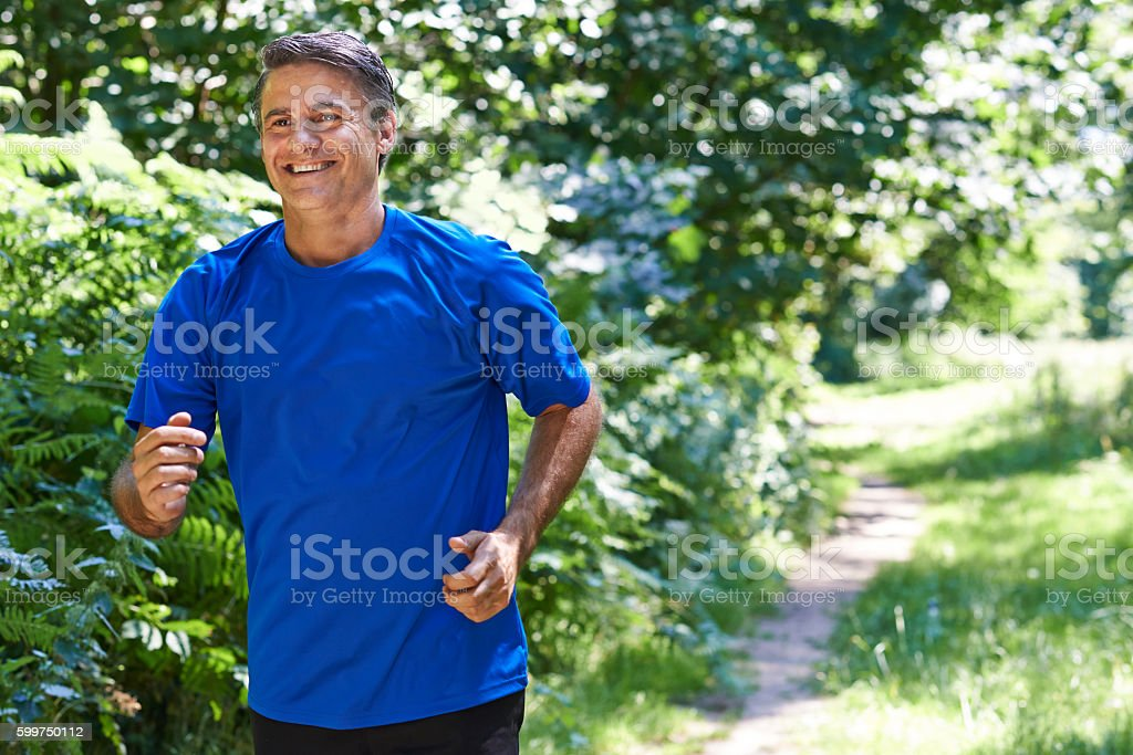 Mature Man Running Outdoors In Countryside stock photo