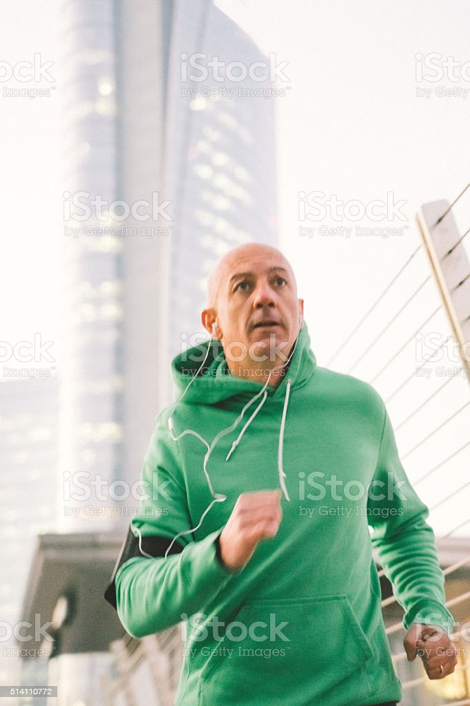 Mature Man Running Outdoors Wearing Sport Clothes stock photo