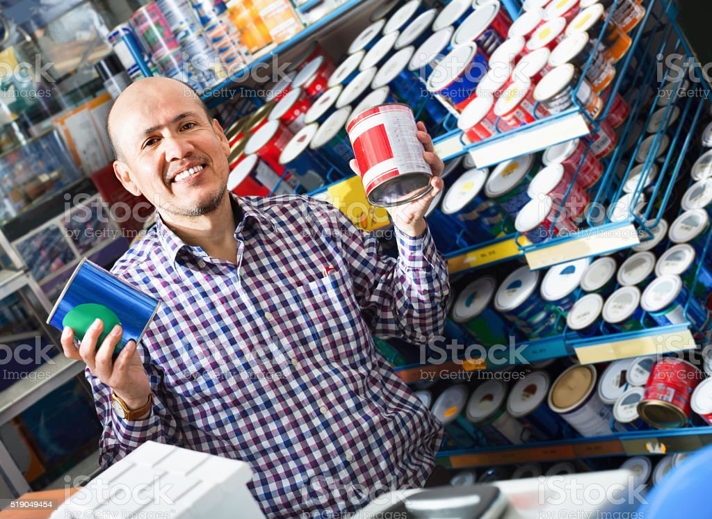 Mature man selecting wall paint and emulsion in store stock photo