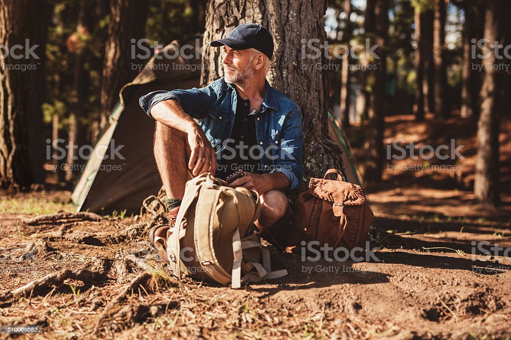 Mature man sitting alone at campsite with backpack stock photo