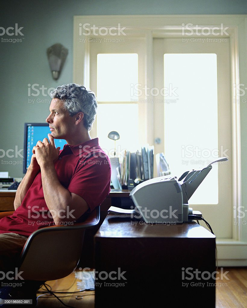 Mature man sitting at home office desk, profile royalty-free stock photo