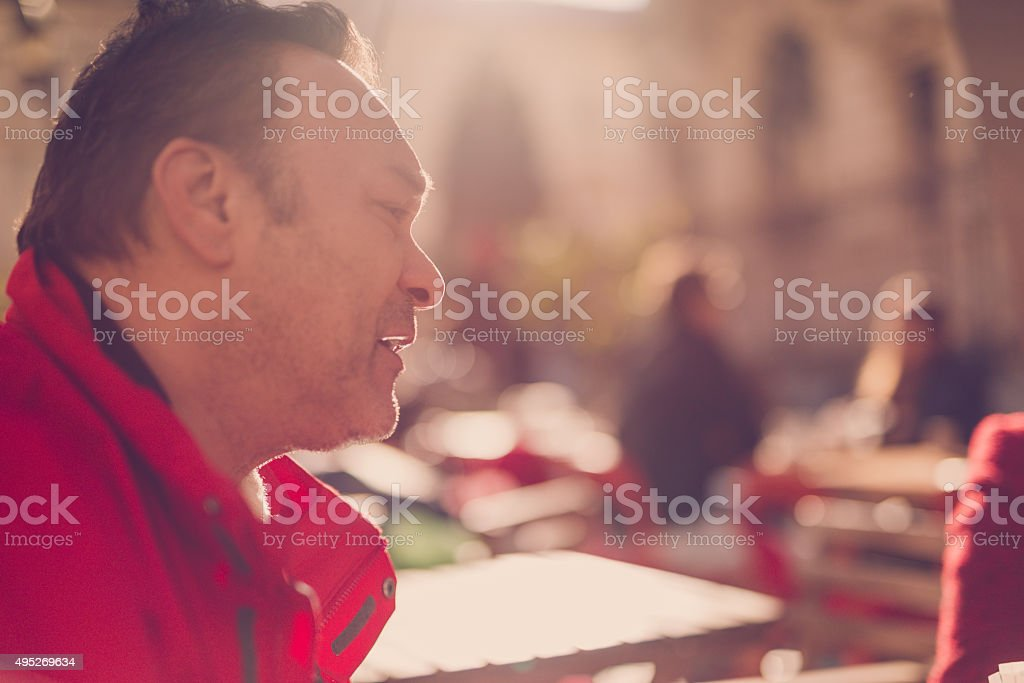 Mature man sitting at on outdoor cafe stock photo