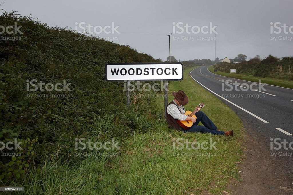 Mature man sitting at roadside with guitar stock photo