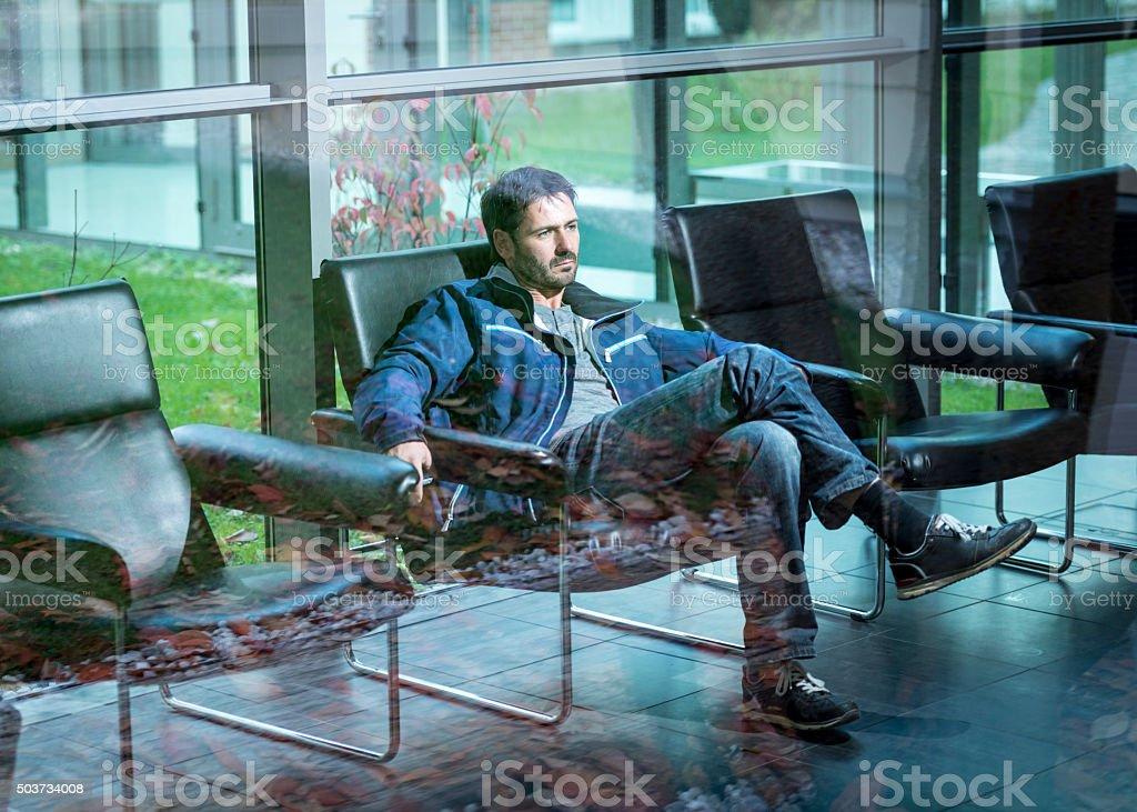 mature man sitting behind window waitingin lobby stock photo