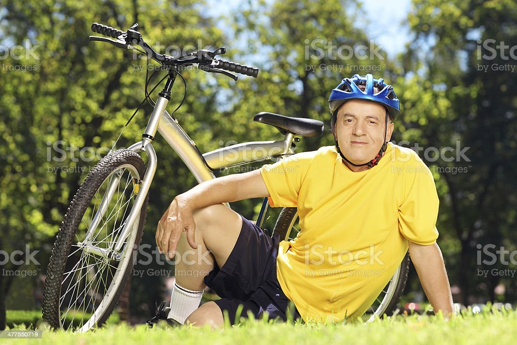 Mature man sitting in park near his bicycle royalty-free stock photo