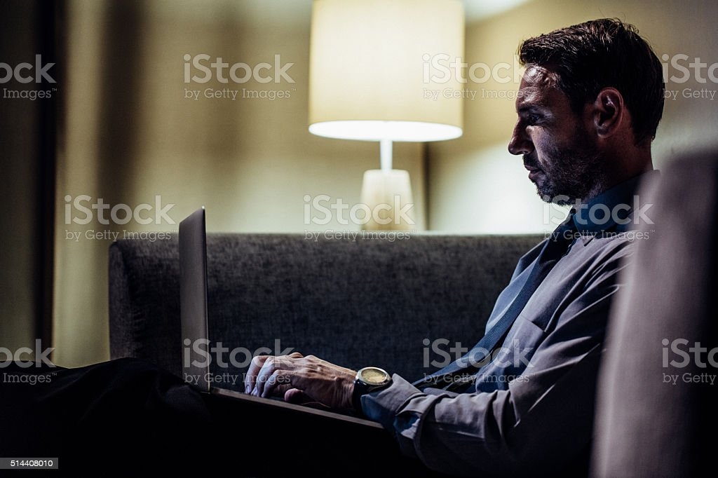 Mature man sitting in sofa and working on laptop stock photo