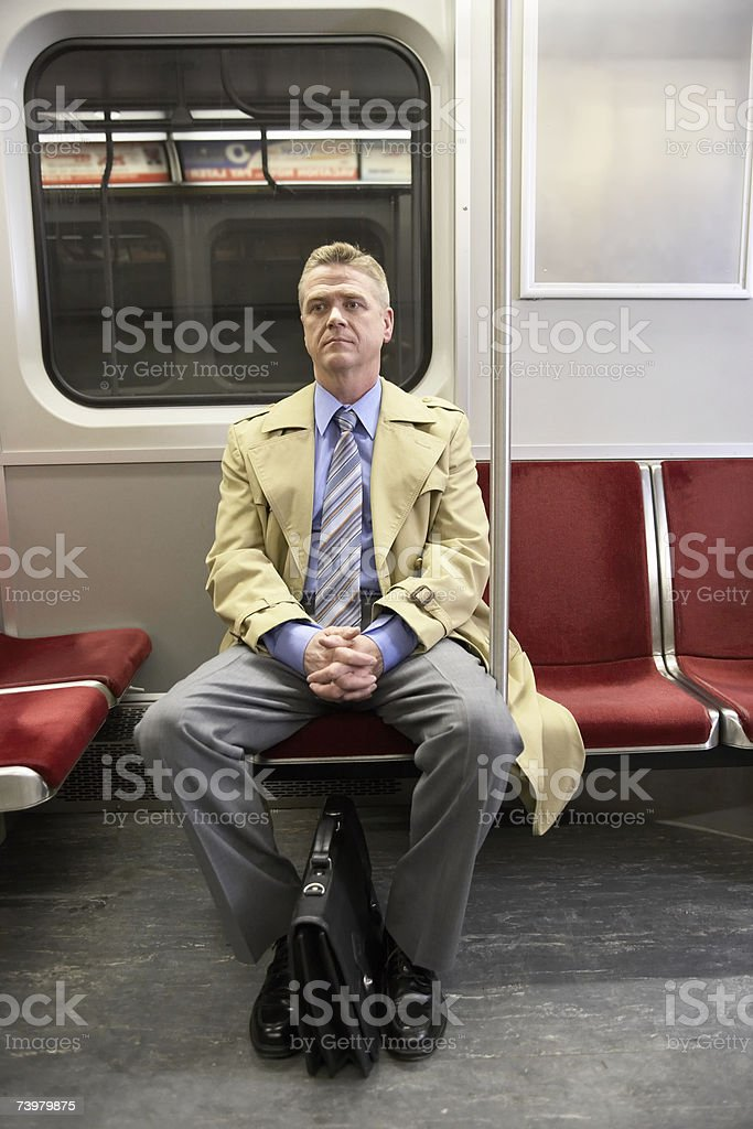 Mature man sitting in subway train, looking away royalty-free stock photo
