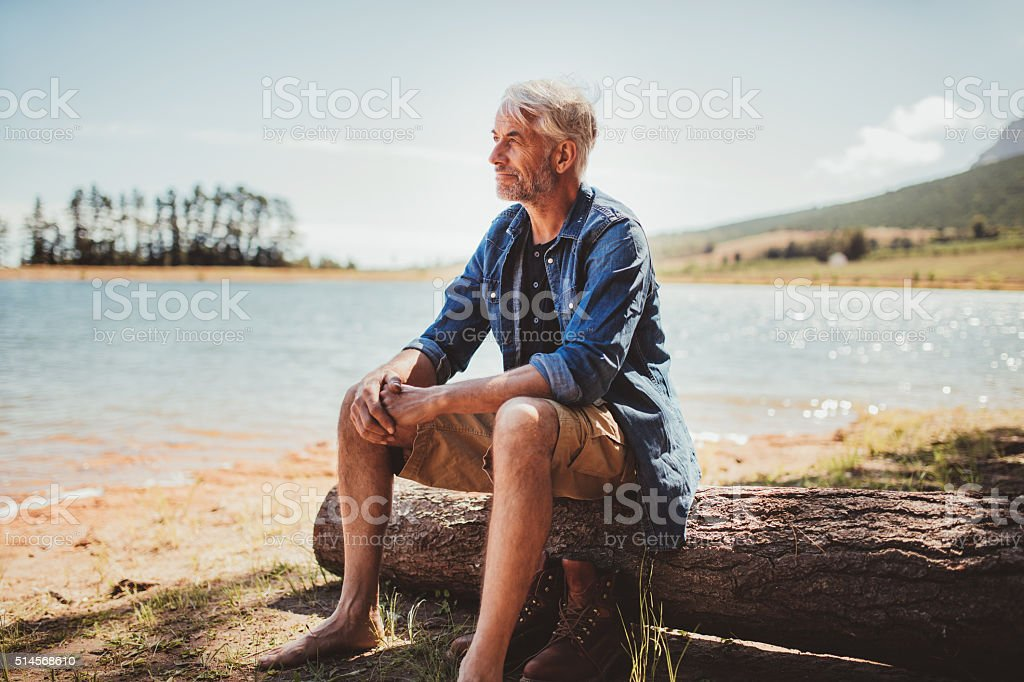 Mature man sitting on a log near lake stock photo