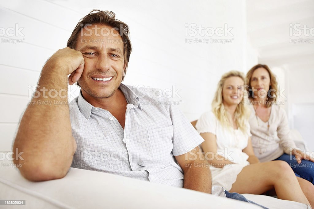 Mature man sitting on a sofa with family royalty-free stock photo