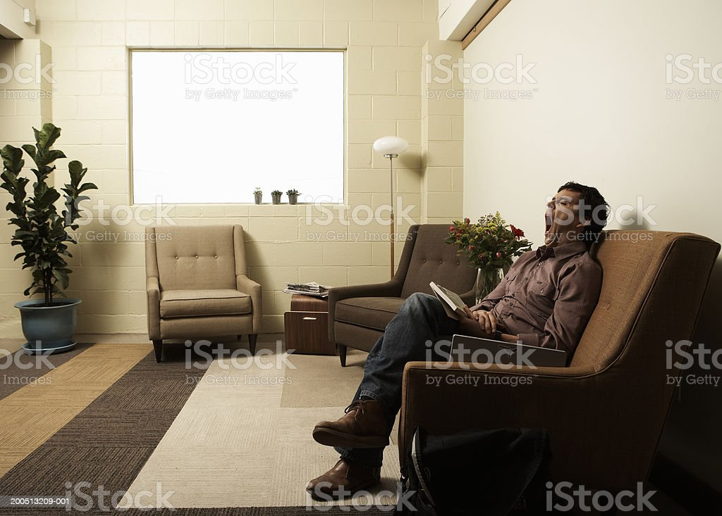 Mature man sitting on armchair, yawning, side view stock photo