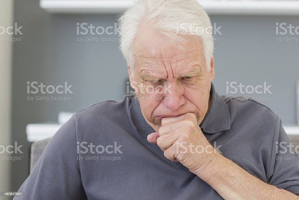 Mature man sitting on sofa coughing stock photo