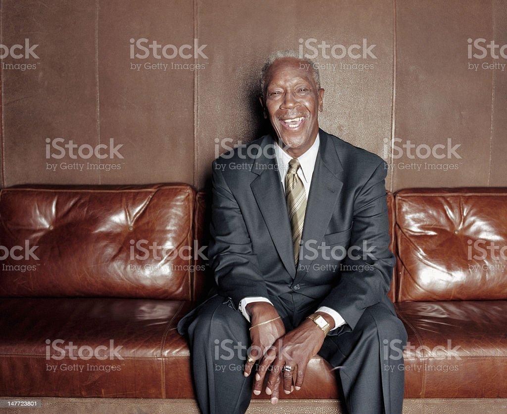 Mature man sitting on sofa, laughing, portrait royalty-free stock photo