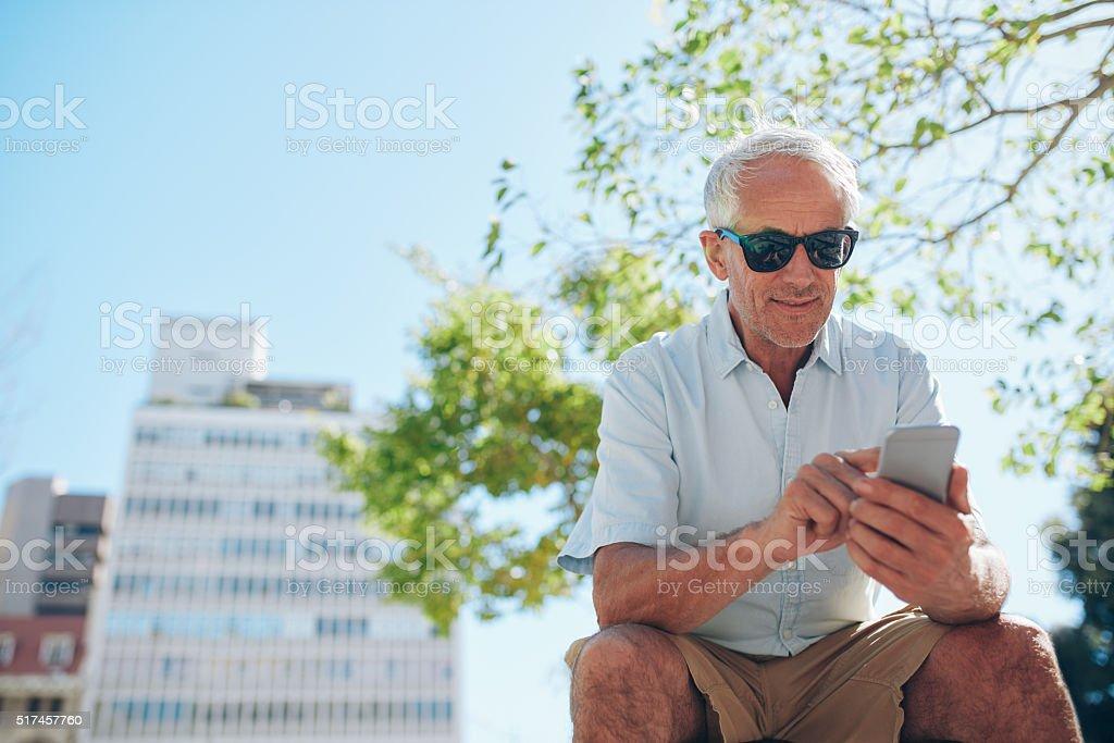 Mature man sitting outdoors using mobile phone stock photo