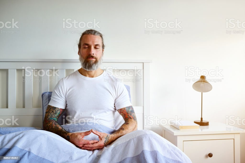 Mature man sitting peacefully on bed stock photo