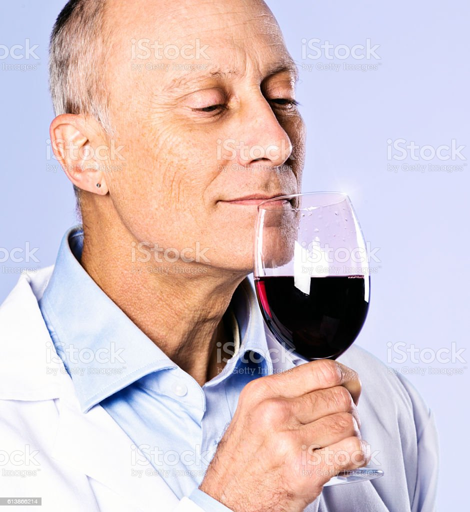 Mature man smiles gently, checking the bouquet  of red wine stock photo