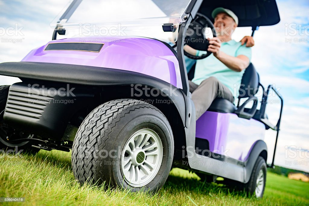 Mature man smiling while driving golf cart stock photo