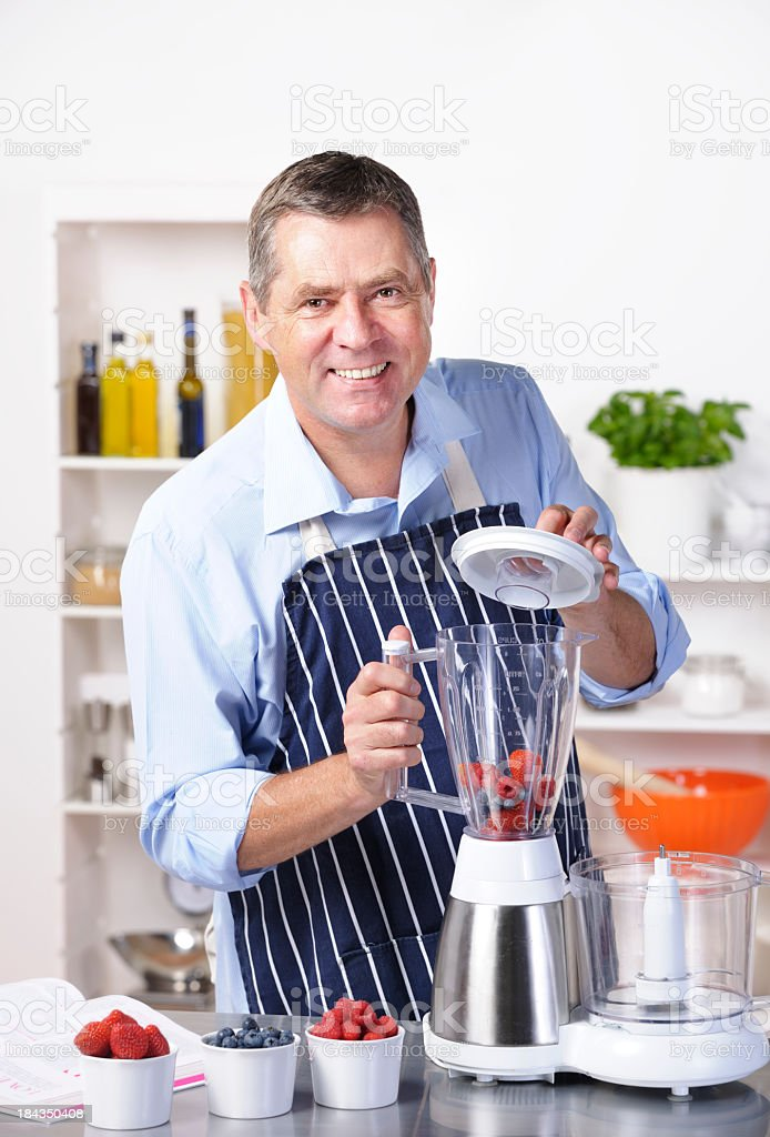Mature Man Smiling While  Making A Healthy Drink/ Dessert royalty-free stock photo