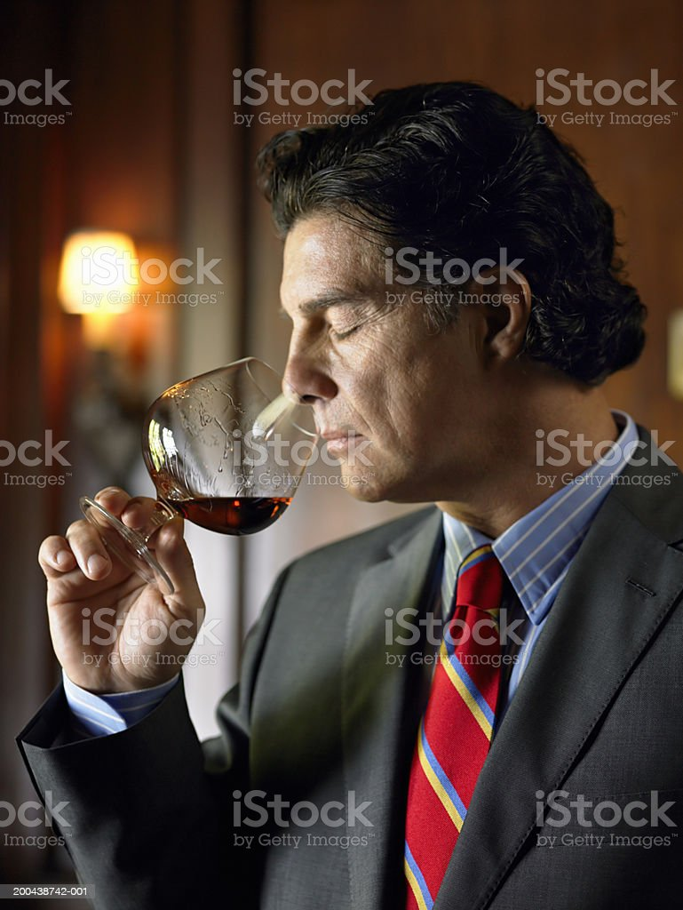 Mature man sniffing brandy from snifter stock photo